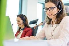 Härlig ung affärskvinna som använder hörlurar med mikrofon med kollegor i bakgrund på kontoret arkivfoto