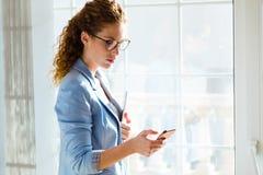 Härlig ung affärskvinna som använder hennes mobiltelefon i kontoret Arkivfoton