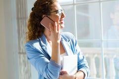 Härlig ung affärskvinna som använder hennes mobiltelefon i kontoret Royaltyfria Bilder