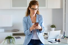 Härlig ung affärskvinna som använder hennes mobiltelefon i kontoret royaltyfri foto