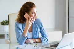 Härlig ung affärskvinna som använder hennes mobiltelefon i kontoret arkivfoto