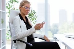 Härlig ung affärskvinna som använder hennes mobiltelefon i kontoret royaltyfri fotografi
