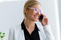 Härlig ung affärskvinna som använder hennes mobiltelefon i kontoret royaltyfria foton