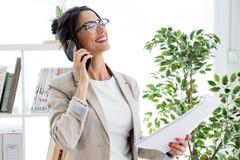 Härlig ung affärskvinna som använder hennes mobiltelefon i kontoret Arkivbilder