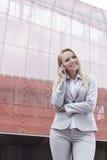 Härlig ung affärskvinna som använder mobiltelefonen, medan stå mot kontorsbyggnad Royaltyfri Foto