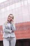 Härlig ung affärskvinna som använder mobiltelefonen, medan stå mot kontorsbyggnad Royaltyfri Bild
