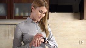 Härlig ung affärskvinna som gör olika gester med henne fingret på pekskärmen av smartwatch lager videofilmer