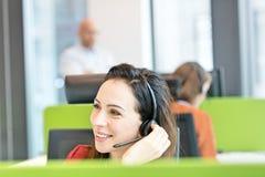 Härlig ung affärskvinna som i regeringsställning använder hörlurar med mikrofon Fotografering för Bildbyråer