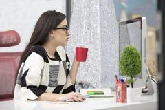 Härlig ung affärskvinna som i regeringsställning dricker kaffe royaltyfri bild