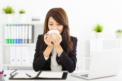 Härlig ung affärskvinna som i regeringsställning dricker kaffe royaltyfri foto