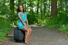 Härlig ung afrikansk amerikankvinna med resväskan på vägen Royaltyfri Foto