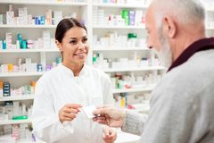 Härlig ung apotekare som säljer läkarbehandlingar till den höga patienten royaltyfri foto