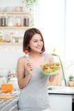 Härlig ung asiatisk flicka som äter sallad le lycklig flickaeati fotografering för bildbyråer