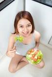 Härlig ung asiatisk flicka som äter sallad le lycklig flickaeati royaltyfri foto