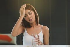 Härlig ung asiatisk kvinna med huvudvärk royaltyfria foton