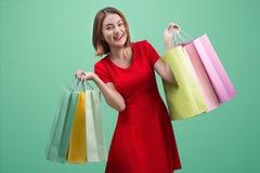Härlig ung asiatisk kvinna med kulöra shoppingpåsar över blått Royaltyfri Foto