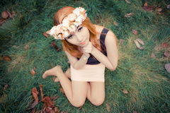 Härlig ung asiatisk kvinna på den gröna ängen med bruna sidor Fotografering för Bildbyråer