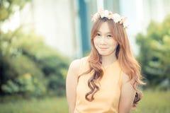 Härlig ung asiatisk kvinna på den gröna ängen med den vita blomman Royaltyfri Foto