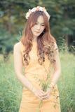 Härlig ung asiatisk kvinna på den gröna ängen med vit flowe Arkivfoto