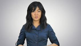 Härlig ung asiatisk kvinna som gör en presentation på vit bakgrund royaltyfri fotografi