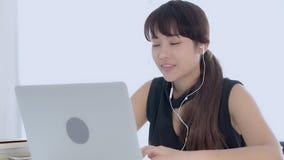Härlig ung asiatisk kvinna som ler att sitta genom att använda lyssnande musik för bärbar datordator med hörluren för för att kop stock video