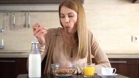 Härlig ung attraktiv kvinna som äter cornflakes för frukost i kök Kupa av kaffe stock video