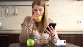 Härlig ung attraktiv kvinna som har frukosten och använder hennes smartphone Dricka fruktsaft arkivfilmer