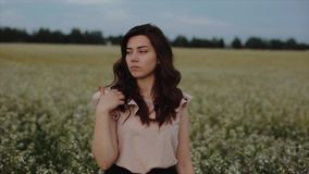 Härlig ung bekymmerslös flicka med långt lockigt hår över bakgrund för landskap för blommavetefält Solnedgångsolskenen stock video