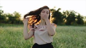 Härlig ung bekymmerslös flicka med långt lockigt hår över bakgrund för landskap för blommavetefält Solnedgångsolskenen arkivfilmer