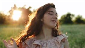Härlig ung bekymmerslös flicka med långt lockigt hår över bakgrund för landskap för blommavetefält Solnedgångsolskenen lager videofilmer