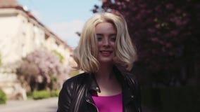 Härlig ung blond flicka med naturlig makeup och tillfälliga kläder som går ner stadsgatan som tycker om sakuraen stock video