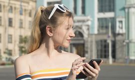 Härlig ung blond flicka på en stadsgata på en solig dag med en smartphone som söker efter något på översikt Royaltyfri Fotografi