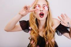 Härlig ung blond flicka som visar fred med den öppnade munnen och att ha gyckel och att posera till kameran som firar händelse sl arkivfoto