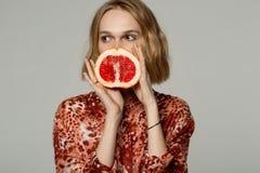 Härlig ung blond flickaholdinghalf av grapefrukten nära framsida royaltyfria bilder