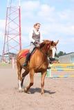 Härlig ung blond häst för kvinnaridningkastanj Royaltyfri Foto