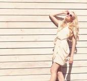 Härlig ung blond kvinna för utomhus- sinnlig modestående för sommar ett vitt klänninganseende på bakgrunden av träplankor ton royaltyfri foto