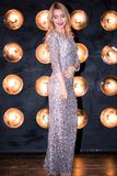 Härlig ung blond kvinna i en lång silverklänning på svart bakgrund med ljus arkivbild
