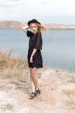 Härlig ung blond kvinna i en svart klänning och en ljus svart hatt i öknen och vinden som blåser hennes hår i en varm sommardag Arkivfoton