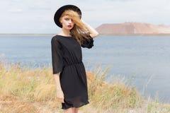 Härlig ung blond kvinna i en svart klänning och en ljus svart hatt i öknen och vinden som blåser hennes hår i en varm sommardag Arkivbilder