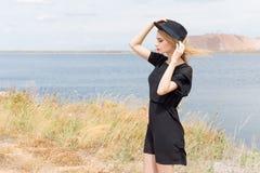Härlig ung blond kvinna i en svart klänning och en ljus svart hatt i öknen och vinden som blåser hennes hår i en varm sommardag Arkivfoto