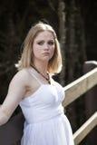 Härlig ung blond kvinna i en vitklänning Royaltyfri Fotografi