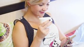 Härlig ung blond kvinna i säng som dricker kaffe och använder smartphonen arkivfilmer