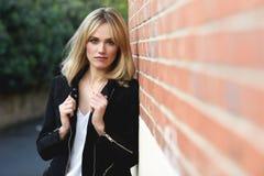 Härlig ung blond kvinna i stads- bakgrund Royaltyfria Foton