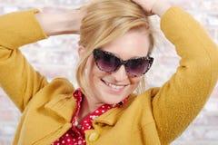 Härlig ung blond kvinna med ett gult omslag arkivbild