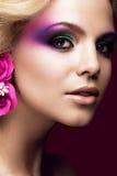 Härlig ung blond kvinna med idérik sminkfärg och blommor på öronen Härlig le flicka Art Makeup royaltyfria bilder