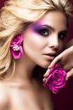 Härlig ung blond kvinna med idérik sminkfärg och blommor på öronen Härlig le flicka Art Makeup arkivbild