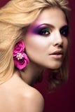 Härlig ung blond kvinna med idérik sminkfärg och blommor på öronen Härlig le flicka Art Makeup fotografering för bildbyråer