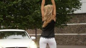 Härlig ung blond kvinna med långt hår som är stående tillbaka nära den vita bilen flickan poserar tillbaka sikt långsam rörelse lager videofilmer