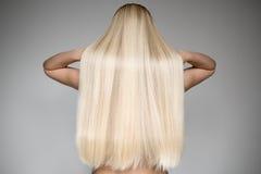Härlig ung blond kvinna med långt rakt hår royaltyfria bilder