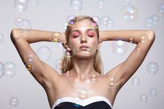 Härlig ung blond kvinna med såpbubblor på grå backgroun royaltyfria bilder